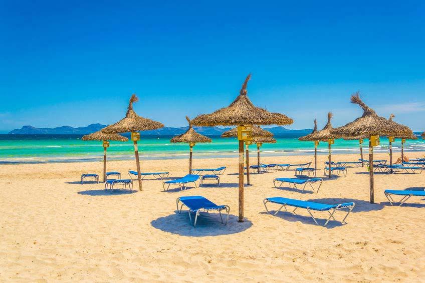 Stranden i Ca'n Picafort med solbrikse og parasoller