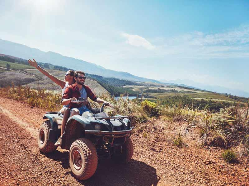 Ungt par kører på en ATV på en dejlig solskinsdag