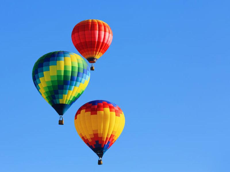 Tre farverige luftballoner på himlen på Mallorca