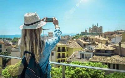 Kvindelig turist med sin smartphone i hænderne fotograferer i Palma de Mallorca under sollys og blå himmel på en solskinsdag