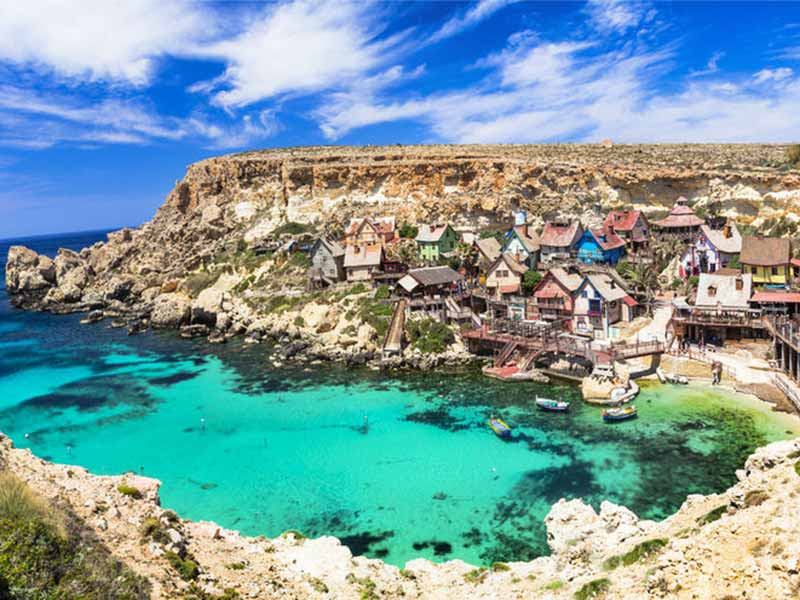 Popeye landsby på Malta omgivet af det dybe blå vand i Middelhavet