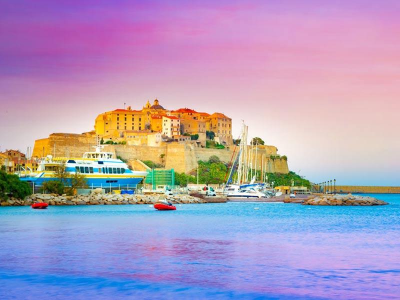 Historiske bygninger og yachtbåde i Calvi havn om natten