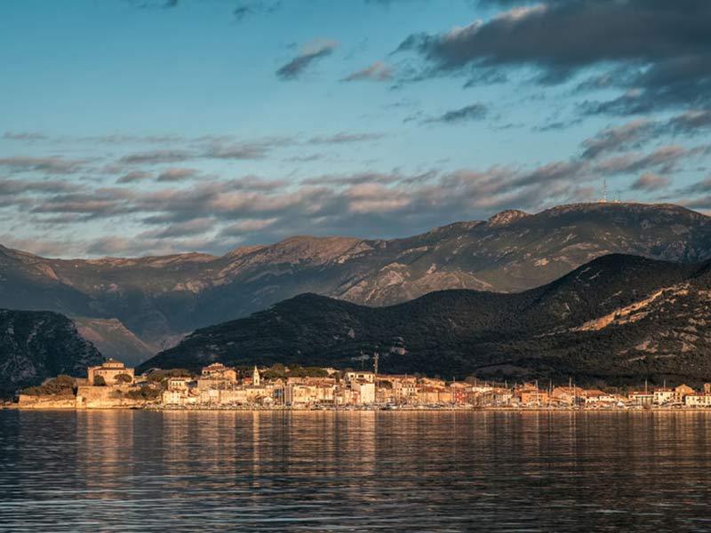 Aftenens solskin oplyser citadellet og bygningerne i Saint Florent på Korsikas kyst med bjerge i baggrunden